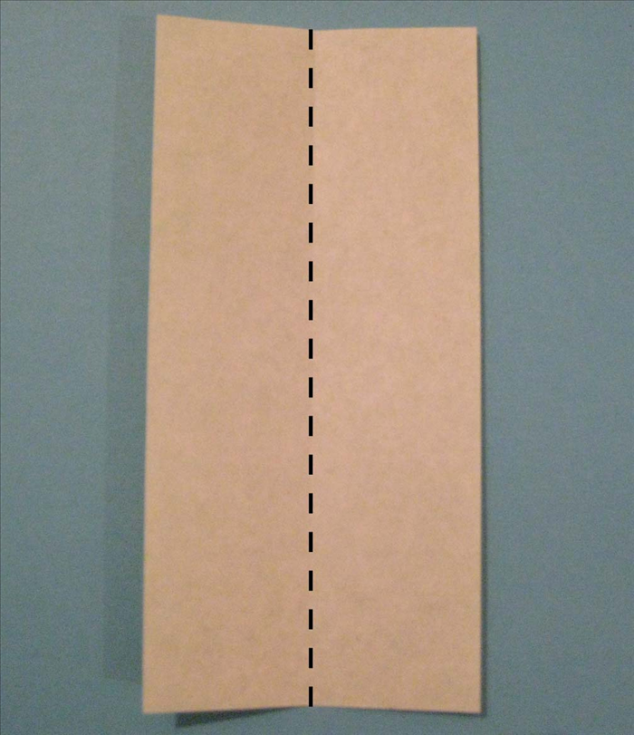 Place the paper with the colored side facing down and the short ends on the top and bottom.  Fold it in half lengthwise. Unfold