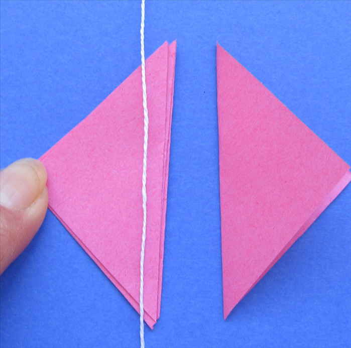 You should have 3 triangles glued and one left over  Place the string near the long edge of the 3 glued triangles Put glue on the 4th triangle and align it on top