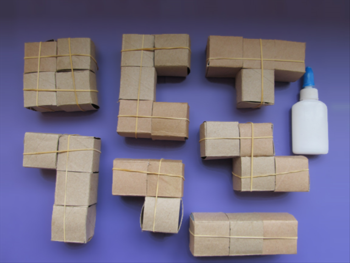 <p> Carefully glue the cubes together as shown in the picture.</p>   <p> Use the rubber bands to hold them together until the glue dries.</p>   <p>  </p>
