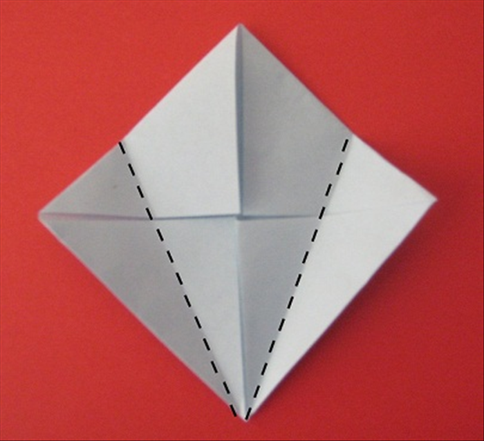 Fold the left and right points towards the center and align the edges with the center crease