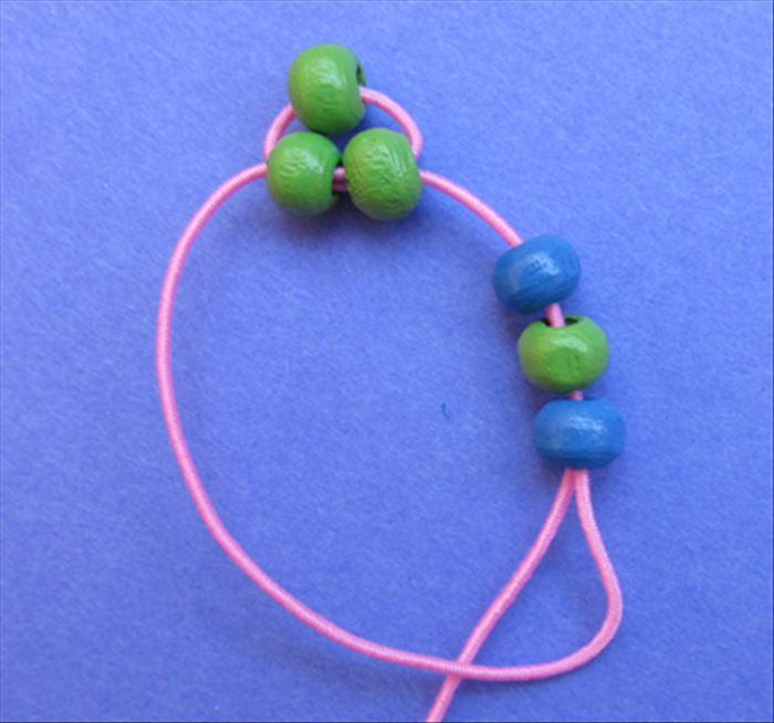 Bring the end of the left string around, into and through the right side of the 3 beads.
