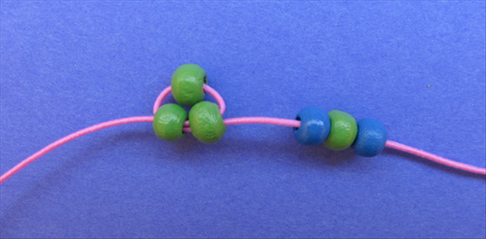 Put 1 blue, 1 green and then another blue bead on the right string.