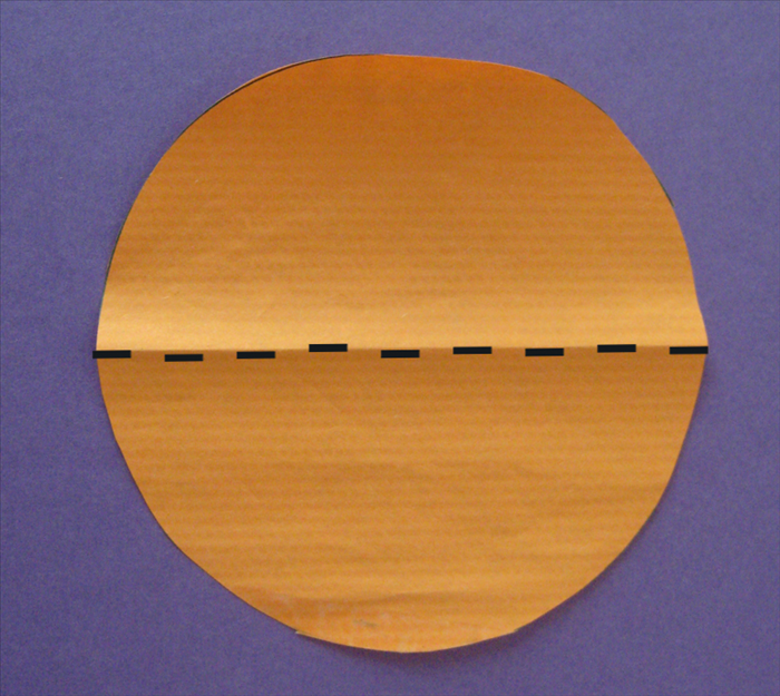 <p> Fold the circles in half</p>