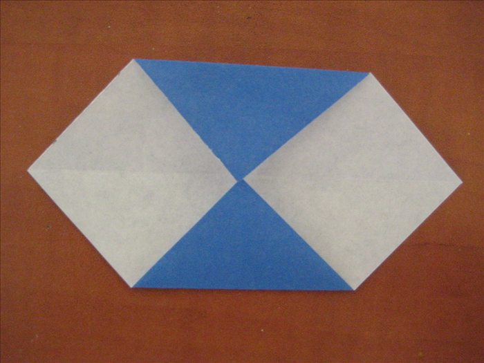 The colored side of the paper should  be on the bottom.  Bring the top and bottom points up to the center crease you just made in the last step.