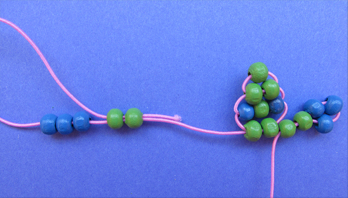 Insert 2 green beads then 3 blue beads on the left side. 