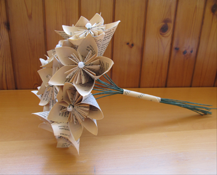 How to make a kusudama bouquet from book pages insert the flower stems into the tube and adjust the flowers to form a slight dome shape mightylinksfo