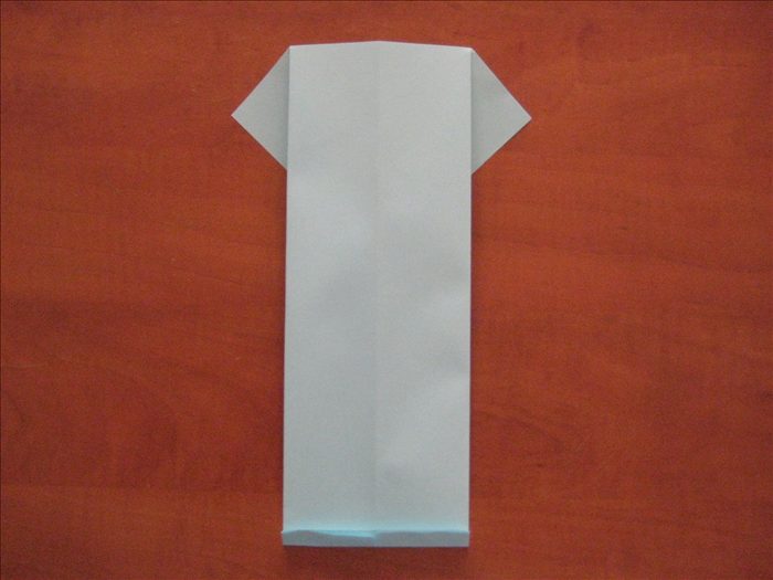 Flip the paper over to the back side. Make a small fold at the bottom. This fold will be the collar.